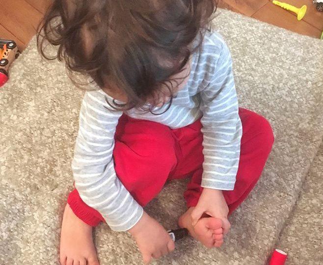 enfant qui s'applique des huiles essentielles sous les pieds